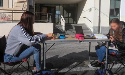 Si mette a studiare con tavolino e pc davanti al liceo, la foto commuove